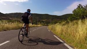 Cyclist descending near Lac Salagou, Languedoc